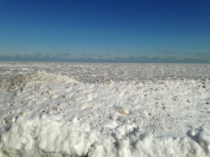 Beachfront snowdrift in front of Lake Michigan ice floes.