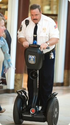 Paul Blart riding a segway.
